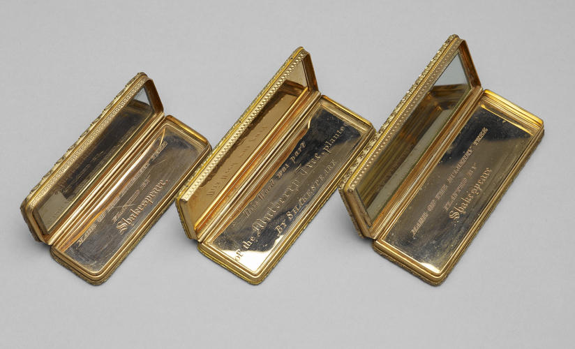Colour photograph of three small wooden boxes, lying open, revealing insides lined with mirrored glass and metal engraved with Shakespeare's name.